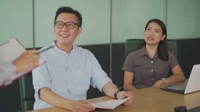 役員室のビジネス会議で発表する同僚に耳を傾けるアジアの中国のホワイトカラー労働者 - white collar worker点の映像素材/bロール