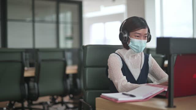 新しいsopと社会的な離れた病気予防の安全対策を使用して検疫後に仕事に戻るアジアの中国の白人首輪労働者女性 - white collar worker点の映像素材/bロール