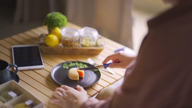 vídeos y material grabado en eventos de stock de mujer china asiática cortando pastel de luna de piel de nieve disfrutando de su té de la tarde con postre del festival tradicional chino en la sala de estar - una mujer de mediana edad solamente