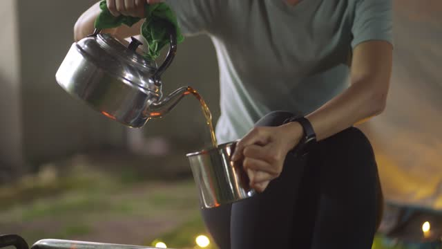 asian chinese woman pouring hot teal from kettle and drinking in front of tent camping at backyard of their house staycation weekend activities - cup stock videos & royalty-free footage