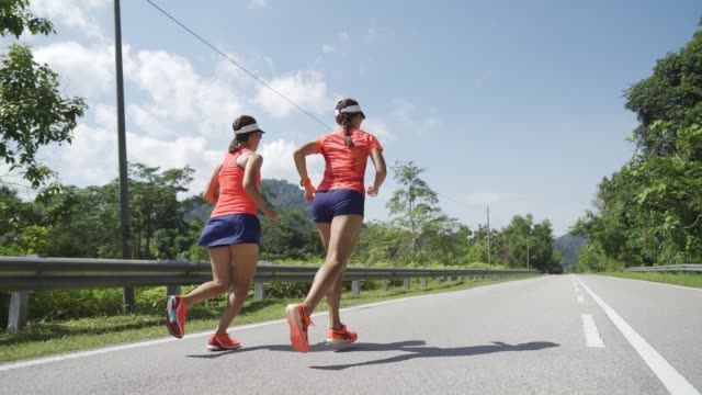 asian chinese woman racer running in country side with her friend - toughness stock videos & royalty-free footage