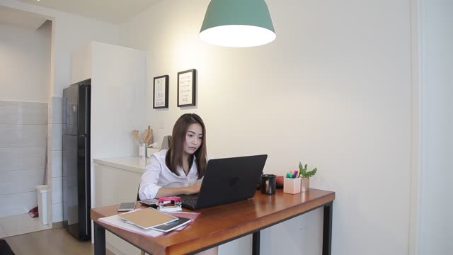 vídeos de stock e filmes b-roll de asian chinese woman using laptop to work at home - plano charriot