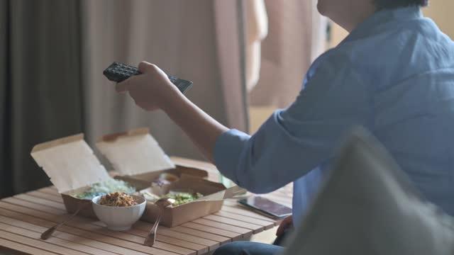 リビングルームのリサイクル紙容器にマレーシア料理ナシケラブ、ナシウラブ、アヤムペルシクを楽しみながら、テレビのリモコン選択チャンネルを使用してアジアの中国人女性 - リサイクル素材点の映像素材/bロール
