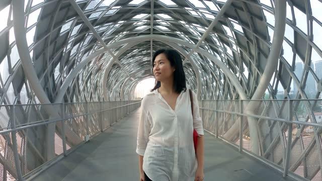 vidéos et rushes de femme chinois asiatique marchant par le pont piétonnier de passerelle dans le centre-ville de kuala lumpur - vue de face