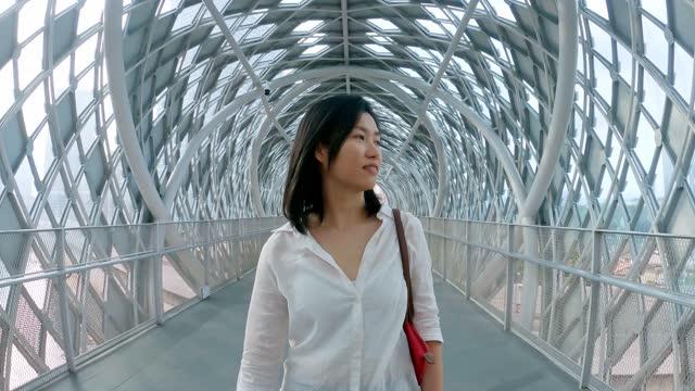 asian chinese woman walking thru pedestrian walkway bridge in kuala lumpur city center - kuala lumpur stock videos & royalty-free footage