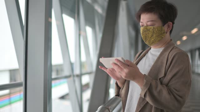 asian chinese woman with protective face mask walking on urban bridge in the city, checking financial stock market analysis with mobile app on smartphone on the go, showing downward trend due to the covid-19 health crisis. business on the go - walkable city stock videos & royalty-free footage