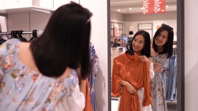 衣料品小売店で買い物やブラウジングアジアの中国人女性 - 鏡点の映像素材/bロール