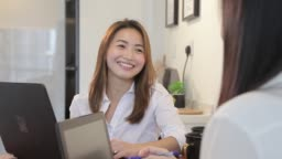 asian chinese women using laptop to work while having conversation at home