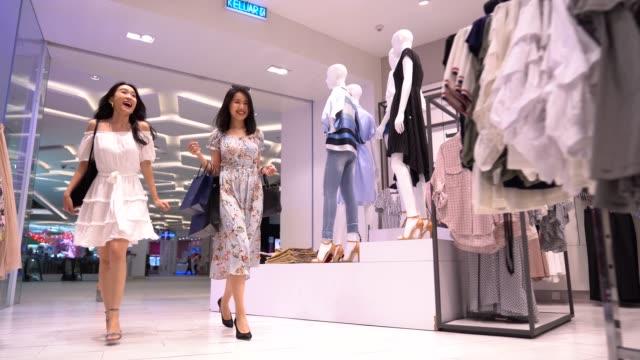 stockvideo's en b-roll-footage met aziatische chinese vrouwen die in kledingopslag lopen om te winkelen - kledingwinkel