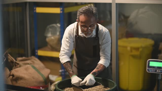 asian chinese working senior man craftsperson scooping raw coffee beans from bucket to weighing machine and blending it for coffee roasting process in factory warehouse - organic stock videos & royalty-free footage