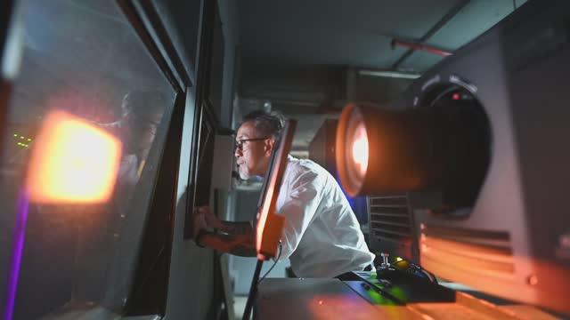 operatore cinematografico senior dal lavoro cinese asiatico che guarda attraverso la finestra dal backstage della movie projection room osservando guardare il film in riproduzione - proiettore cinematografico video stock e b–roll