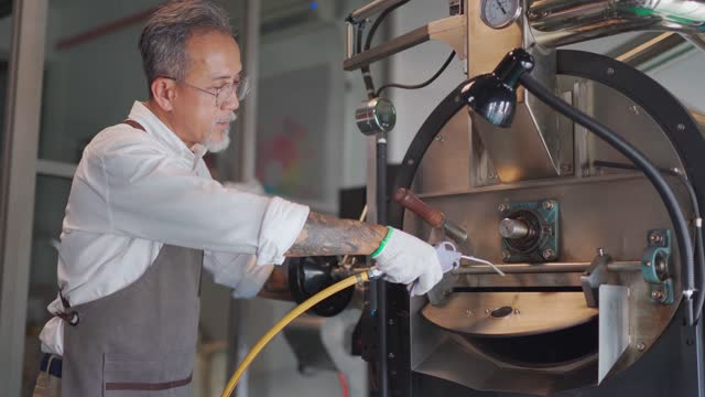 asian chinese working senior man with glove brushing and cleaning coffee roaster machine with vacuum cleaning - man and machine stock videos & royalty-free footage