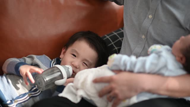 asian chinese young boy drinking water lying down on sofa with his family in living room - two parents stock videos & royalty-free footage