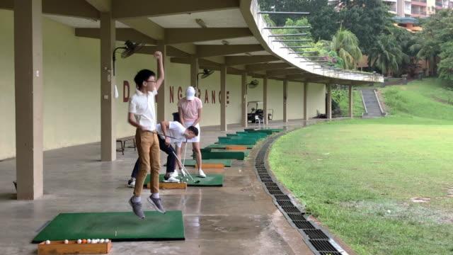 vidéos et rushes de jeune garçon chinois asiatique heureux et sautant vers le haut après son poing teeing outre du club de conducteur au secteur de conduite de golf - terrain de golf