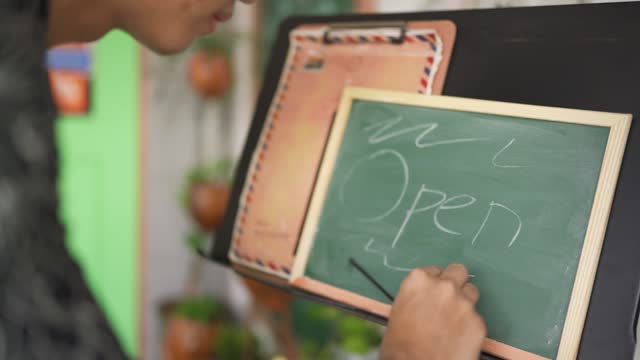 """asian chinese young cafe barista waiter cafeteria worker writing """"open"""" word using chalk on blackboard outside of cafe restaurant preparing to open for business in the morning - one teenage boy only stock videos & royalty-free footage"""