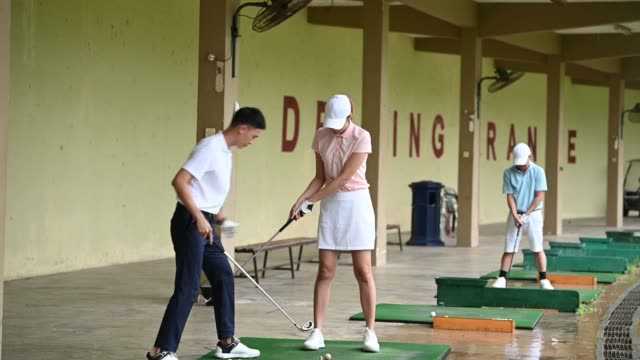 asian chinese young couple practice playing golf at golf driving range - golf shoe stock videos & royalty-free footage