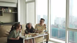 Asian chinese young family enjoying take out food in front of tv in living room during weekend