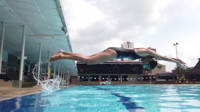 asian chinese young female sportperson dive into water - swimming pool stock videos & royalty-free footage
