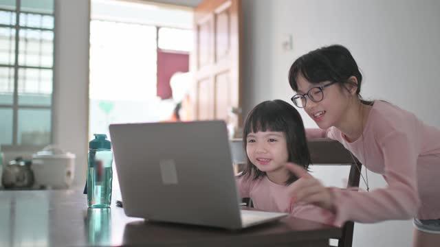 vídeos y material grabado en eventos de stock de asiática china joven que asiste a clase en línea en la mesa de comedor de la cocina con la ayuda de su hermana - evento virtual