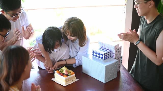 週末に家の裏庭で彼女の家族と彼女の誕生日を祝うアジアの中国の若い女の子 - 囲む点の映像素材/bロール