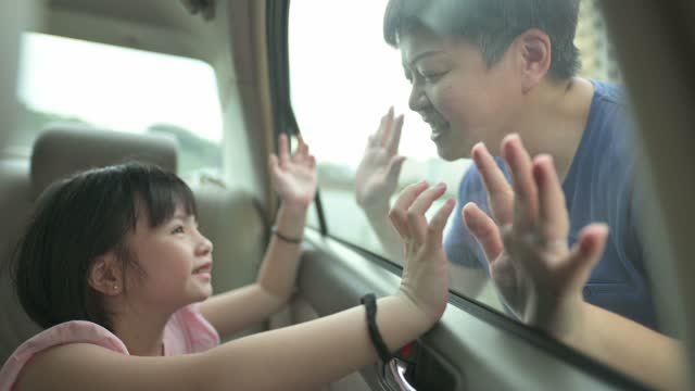 asian chinese young girl inside car looking at her mother through window happily touching - greeting stock videos & royalty-free footage