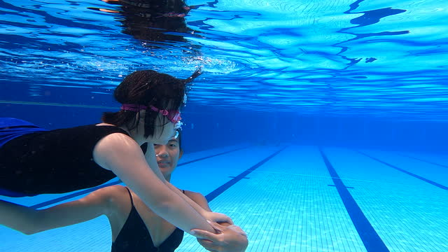 asian chinese young girl practicing breathing exercise in the water with her coach - swimming costume stock videos & royalty-free footage