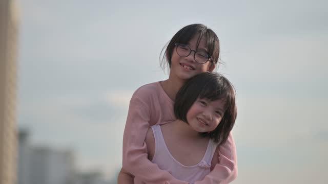 彼女の妹とフェイスマスクで夜の屋外で笑顔アジアの中国の若い女の子 - 子供2人の家庭点の映像素材/bロール