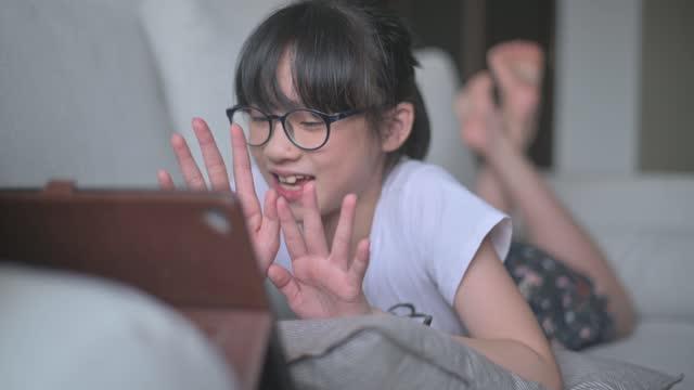asiatiska kinesisk ung flicka pratar med sin far med hjälp av digital tablett på nätet i vardagsrum liggande på soffan glatt - vidbild bildbanksvideor och videomaterial från bakom kulisserna