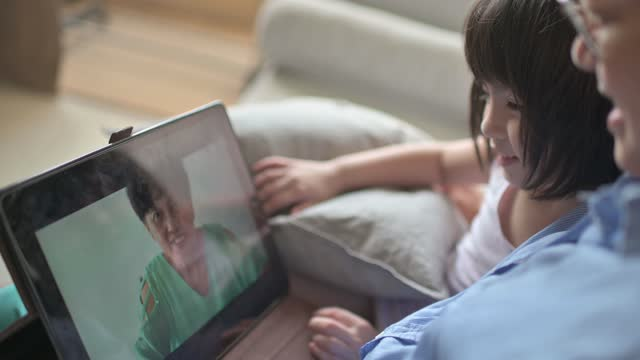 asian chinese young girls talking to her grandmother using digital tablet online in living room on sofa happily with her mother beside - little girl webcam stock videos & royalty-free footage