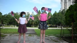 2 asian chinese young girls waving malaysia national flag at public park with face mask