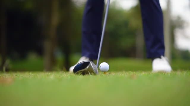 asian chinese young male golfer teeing off and swing his driver club on the golf course - golf swing stock videos & royalty-free footage