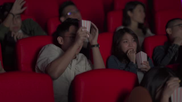 asian chinese young man spill popcorns backward to other audience get a shock from scary movie scene - popcorn stock videos & royalty-free footage