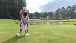 Asian chinese young mother golfer teaching her daughter to playing golf on the golf course