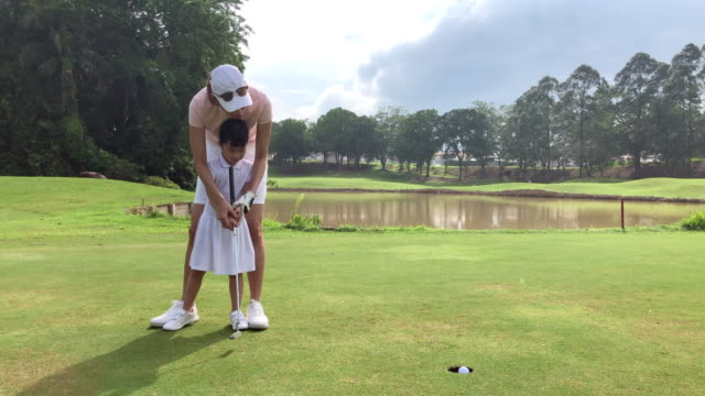 asian chinese young mother golfer teaching her daughter to playing golf on the golf course - golf stock videos & royalty-free footage