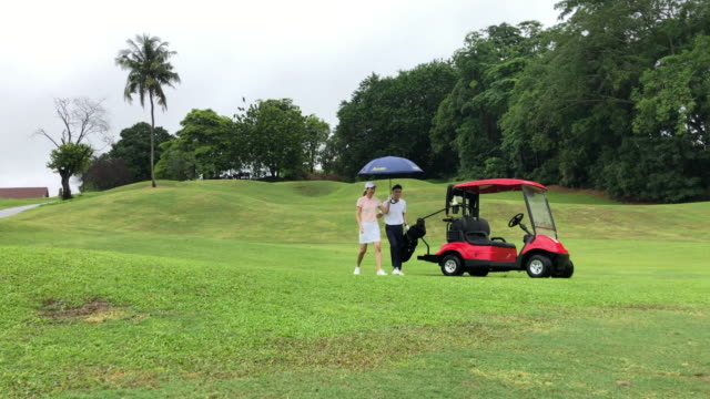 asian chinese young smiling couple golfer riding in a golf cart, getting ready on a golf course - golf bag stock videos & royalty-free footage