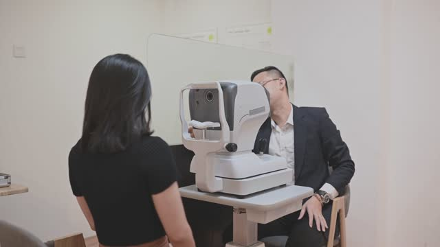 asian chinese young woman having an eye exam at ophthalmologist's office - lens optical instrument stock videos & royalty-free footage