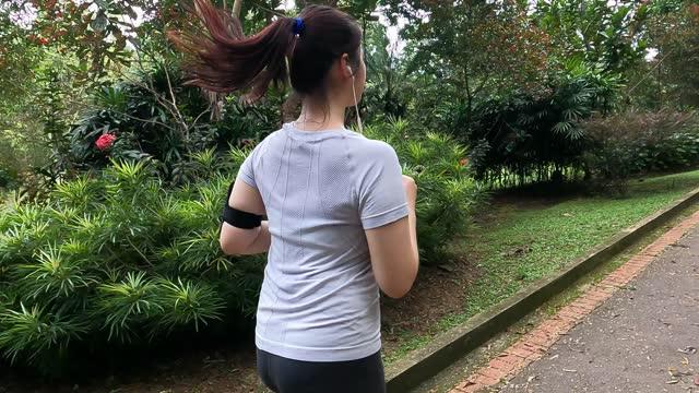 stockvideo's en b-roll-footage met aziatische chinese jonge vrouw die in het park tijdens weekendochtend loopt - jogster