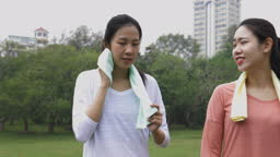 Asian chinese young women talking after workout morning exercise in public park