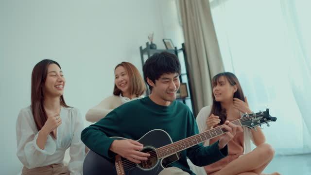 vidéos et rushes de bonheur asiatique de groupe d'ami étroit avec la musique jouée par la guitare en vacances. - singer