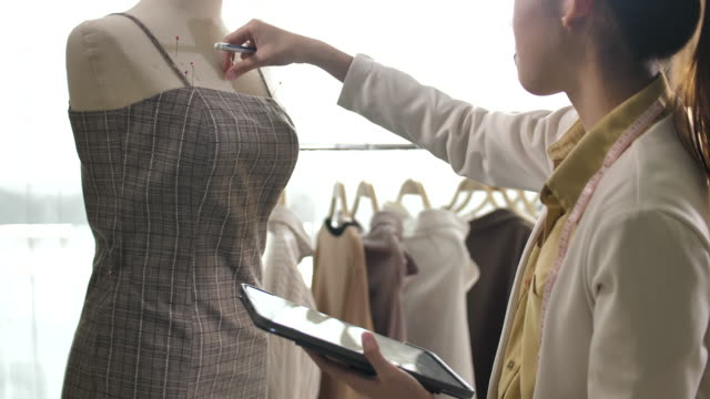 asian clothing designer woman is working with digital tablet - textile industry stock videos & royalty-free footage
