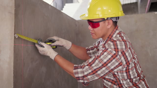 asian construction engineer in hardhat measuring wall with tape at construction site, engineers at work checking construction building project with laser level machine during measurement work on site - tape measure stock videos & royalty-free footage
