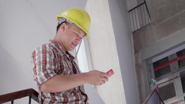建設現場で携帯電話を使用してハードハットでアジアの建設エンジニアを使用してハードハットのアジア建設エンジニア、建設現場で現場の建設建設プロジェクトをチェックする作業エンジ� - 操作する点の映像素材/bロール