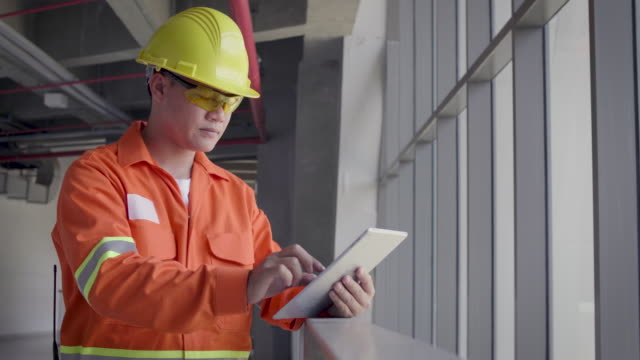 asian construction or electronics engineer in hardhat wearing safety jacket using a digital tablet computer next to window at construction site, engineers at work checking construction building project on site - examining stock videos & royalty-free footage