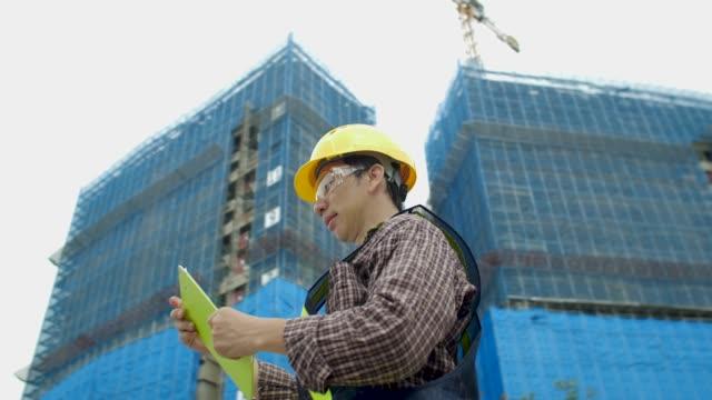 建設現場でのアジアの建設労働者 - ヘルメット点の映像素材/bロール
