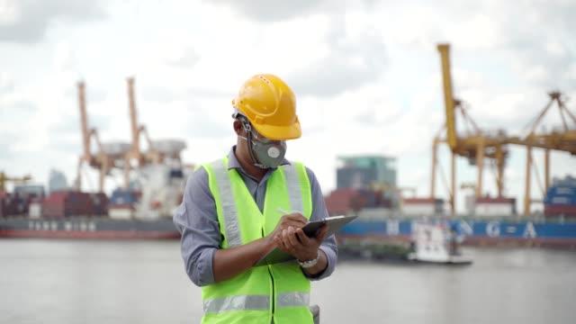 vídeos de stock, filmes e b-roll de trabalhadores da construção asiática trabalhando no canteiro de obras que é importante para a indústria sob supervisão da construção - máscara