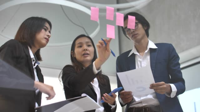 asian corporate discussing business strategies using adhesive notes in office - cultures stock videos & royalty-free footage