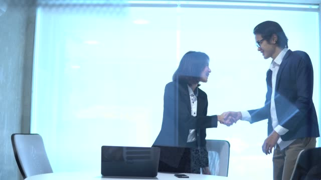 Asian corporate executives greeting business visitor