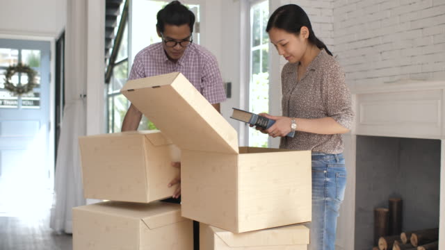 Asian Couple carrying moving boxes and Unpacking After Moving into their new home