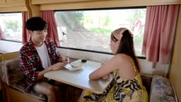 Asian couple eating food together in camper van on vacation