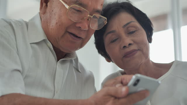 asian couple elderly age 60-70 yearold watching online content in a smart phone while discussion and sitting on a sofa at nursing home in the living room.senior technology concept. - health technology stock videos & royalty-free footage